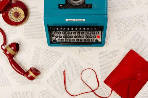Still life macchina da scrivere olivetti, telefono rosso vintage, taccuino rosso